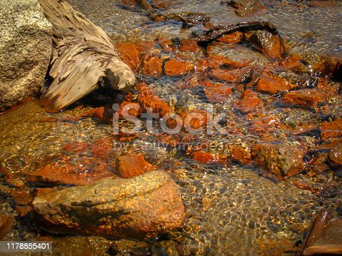 Rippled water wave pattern with sunlight reflection flowing over rocks and pebbles in a shallow stream bed.  Many rocks are orange and red from iron oxide minerals.