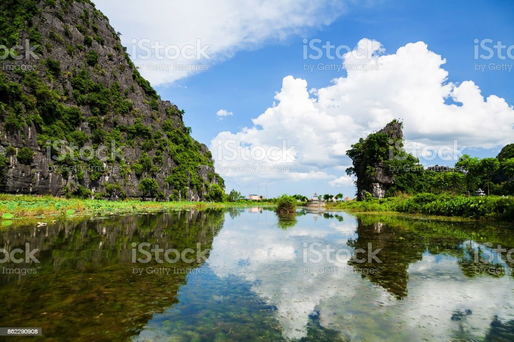 Beautiful scenics landscape of karst mountains with clear blue sky and white cloud reflected in water of Ngo Dong River at Tam Coc portion, Ninh Binh stock photo