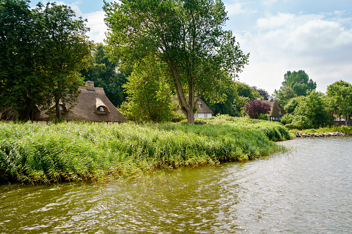 Beautiful Schlei region in Germany, Schleswig Holstein. German landscape in summer. Schlei river and typical houses with thatching, water reed roofs. Sieseby village