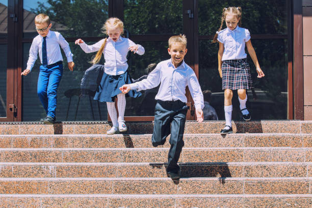 Beautiful school children active and happy on the background of school in uniform stock photo