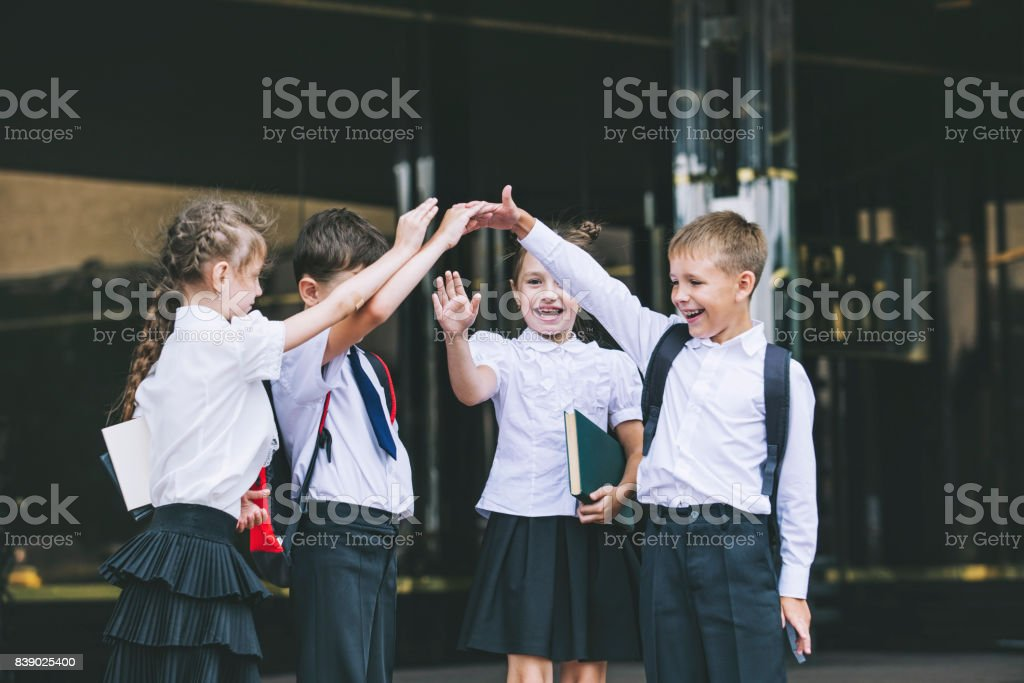 Beautiful school children active and happy on the background of school in uniform royalty-free stock photo