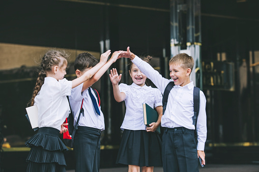 Beautiful School Children Active And Happy On The Background Of School In Uniform Stock Photo - Download Image Now