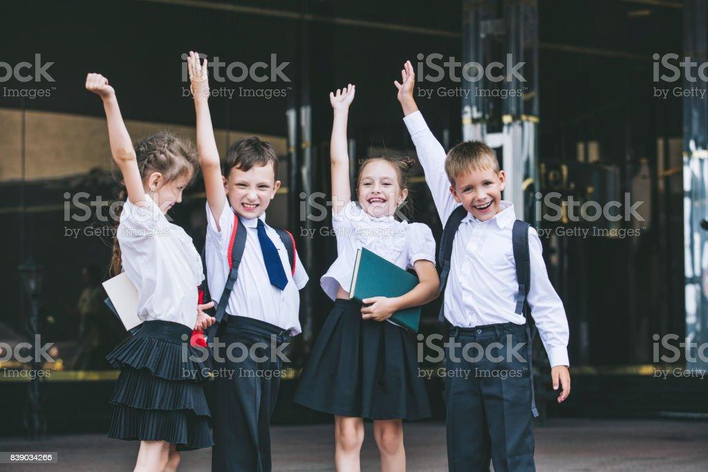 Hermosos niños activados y felices en el fondo de la escuela en uniforme - foto de stock