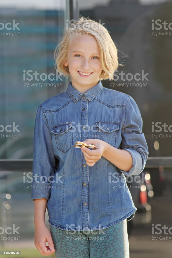 A beautiful school girl playing with a gold fidget spinner. Popular toy. stock photo