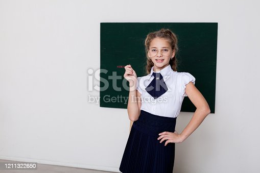 157687202 istock photo Beautiful schoolgirl girl at the board in class in class 1211322650