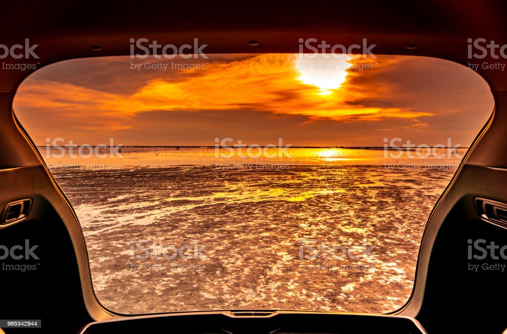 Beautiful sea view from inside car trunk. Sea view with orange sky and clouds in sunset time at the beach. Freedom summer travel with road trip on vacation concept. Romantic view in the evening. zbiór zdjęć royalty-free