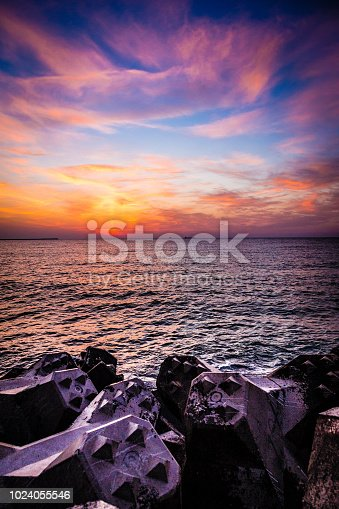 Panoramic color image depicting a beautiful sunrise or sunset on the Black Sea coast in Romania. The sky looks like it's on fire as the sun begins to descend below the horizon. The image is very peaceful and calming. Room for copy space.