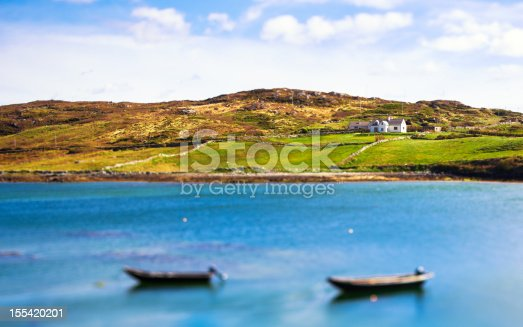 A white house on a hill with two boats in the sea. Tilt shift lens.