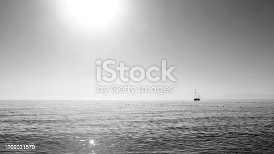 Beautiful seascape. Minimalistic view of the sea and sailing ship in the early morning. Sailing in the sea in the morning sunlight. Mediterranean sea, Turkey. Black and white photo