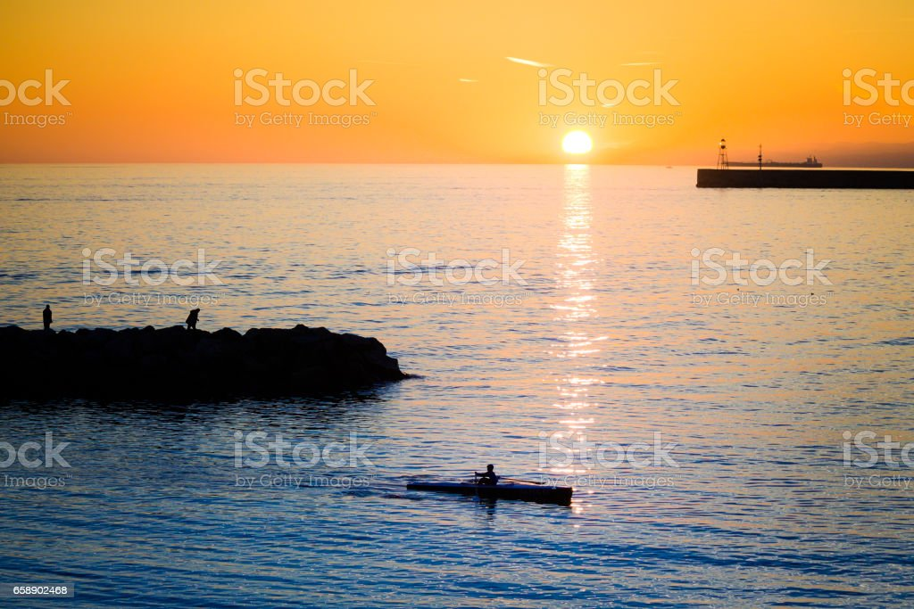 Beautiful seascape sunset time with kayaking kid silhouette. stock photo