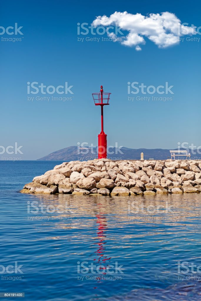 Beautiful seascape with lighthouse. Calm sea and a lighthouse on the pier. Red white solitary pulp. stock photo