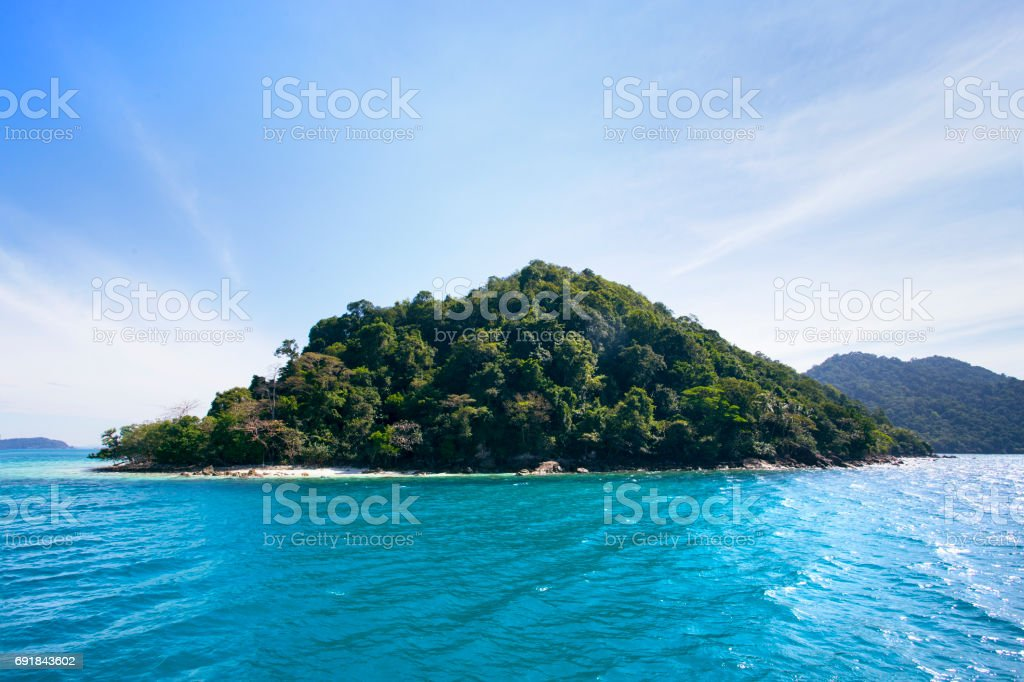 Beautiful seascape with lonely island and secret beach in the bright daylight with summer air and perfect weather for active tourism stock photo