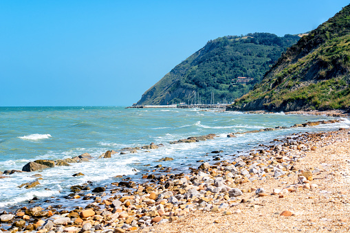 Beautiful seascape with view on sea and mountains on summer day, sea shore with pebble stones and cutwater. Adriatic coast, Rimini, Italy, view from Gabicce Mare