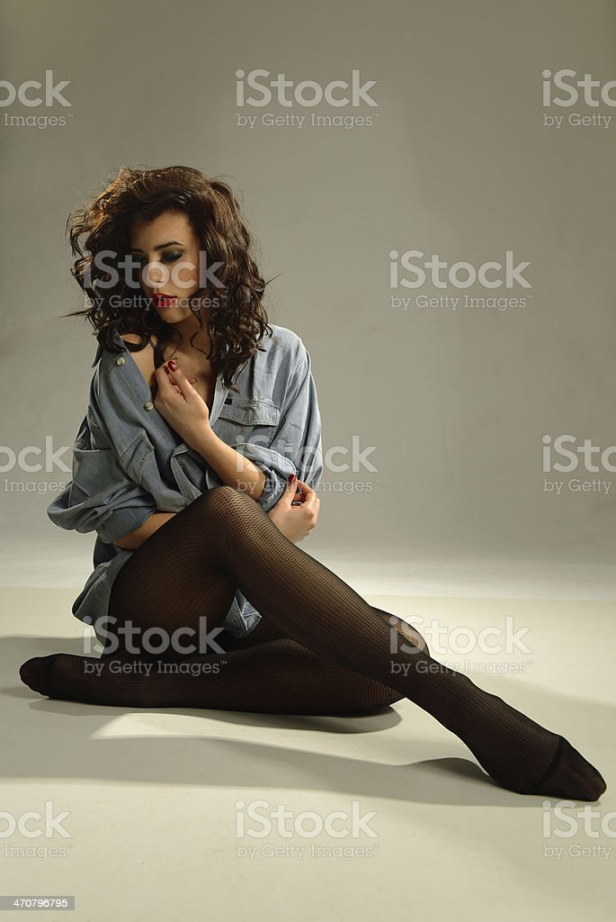 Beautiful seductive fashion model with pantyhose stockings posing in studio royalty-free stock photo