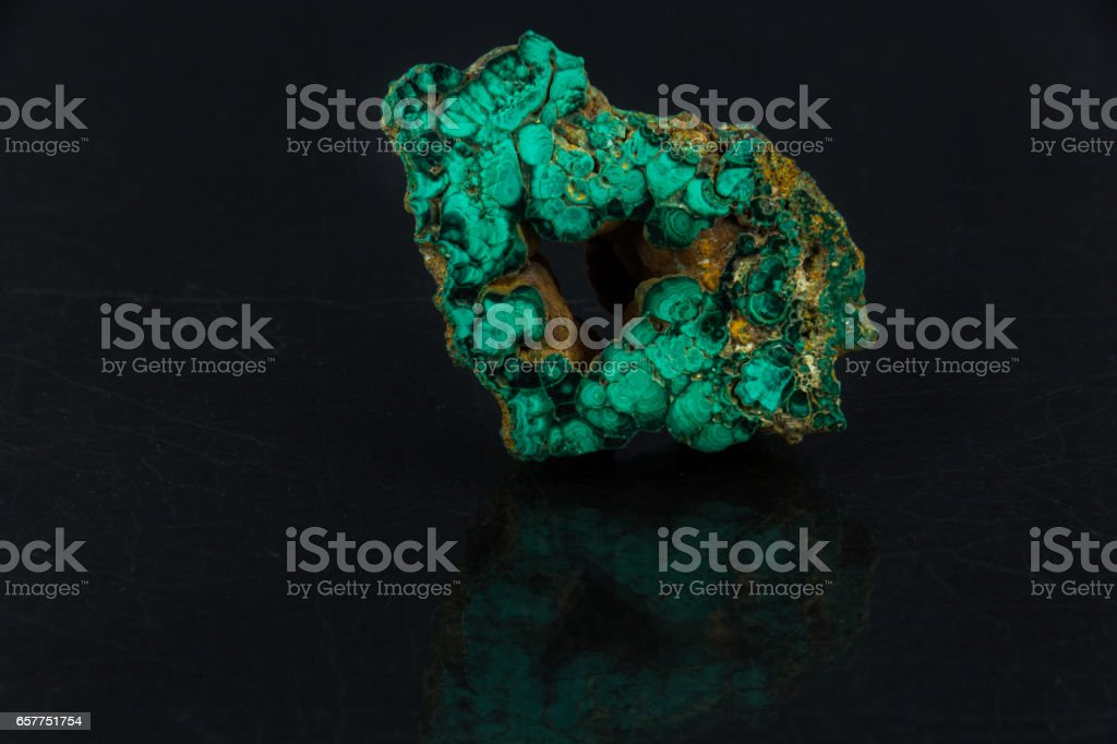 Beautiful semi-precious stone on green malachite  a black background stock photo