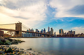 Beautiful sence of Brooklyn bridge and lower manhattan of New York city in dusk evening. Downtown of lower Manhattan of New York city and Smooth Hudson river with sunset light.