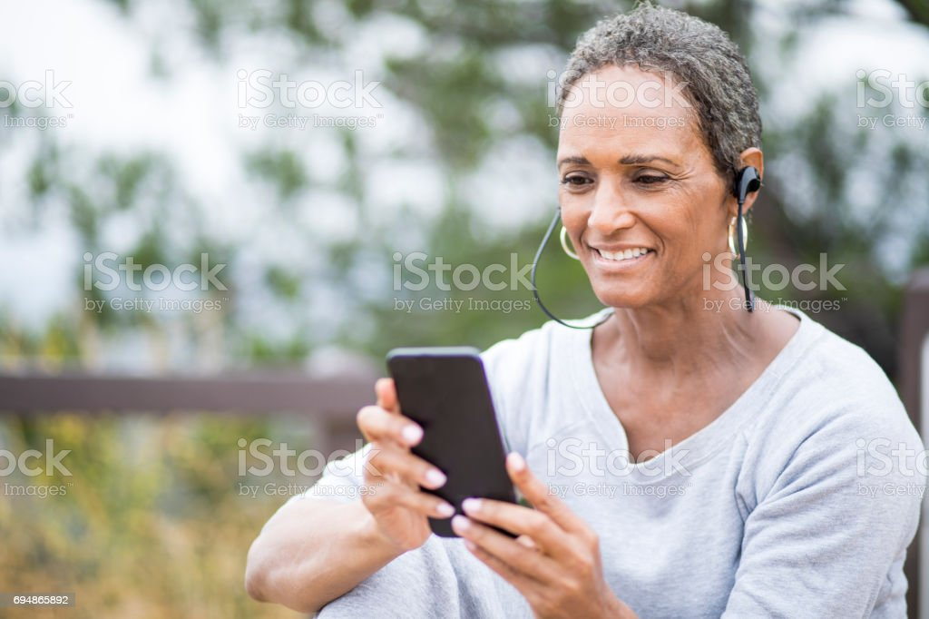 A beautiful senior African American Woman Using Smartphone stock photo