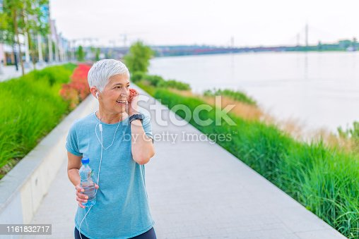 istock Beautiful senior blonde woman running at the park on a sunny day. 1161832717
