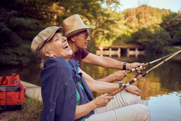 beautiful senior couple enjoying on the lake fishing and having fun stock photo
