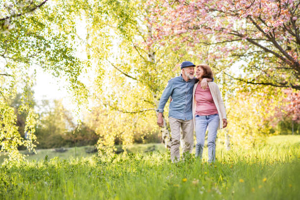 beautiful senior couple in love outside in spring nature. - spring stock pictures, royalty-free photos & images