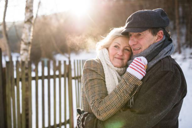 beautiful senior couple on a walk on sunny winter day - wintermantel damen wolle stock-fotos und bilder
