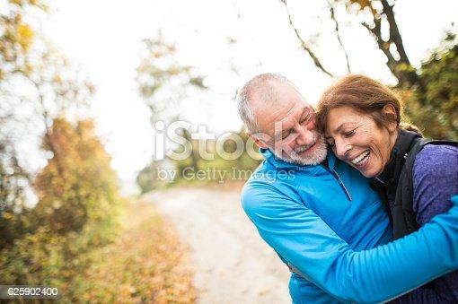 istock Beautiful senior couple running outside in sunny autumn forest 625902400