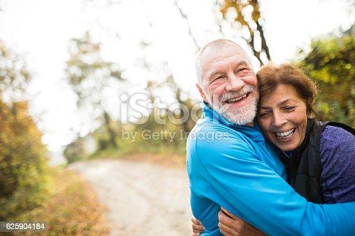 istock Beautiful senior couple running outside in sunny autumn forest 625904184