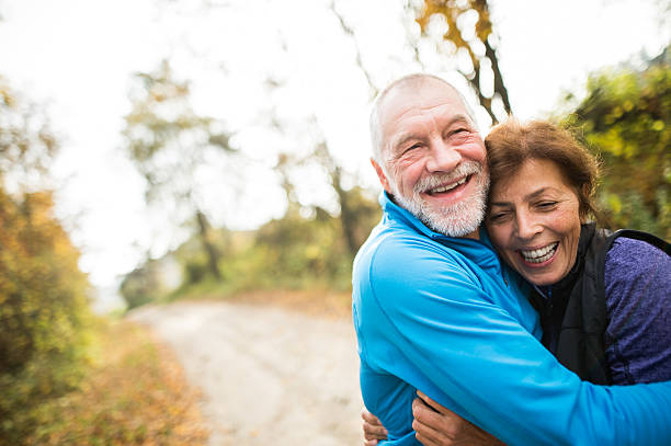 Beautiful senior couple running outside in sunny autumn forest stock photo