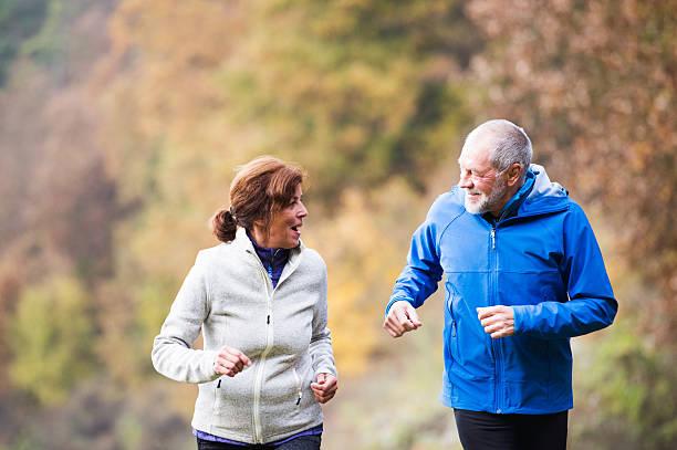 beautiful senior couple running outside in sunny autumn nature - damenjacken stock-fotos und bilder
