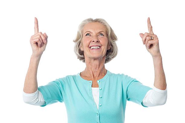 Beautiful senior lady pointing upwards stock photo