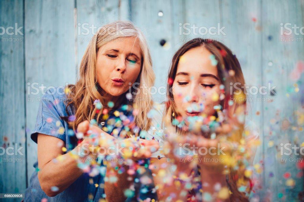 Hermosa madre senior y adulto hija celebrar soplando confetti - foto de stock