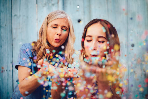 Beautiful senior mother and adult daughter celebrating by blowing confetti stock photo