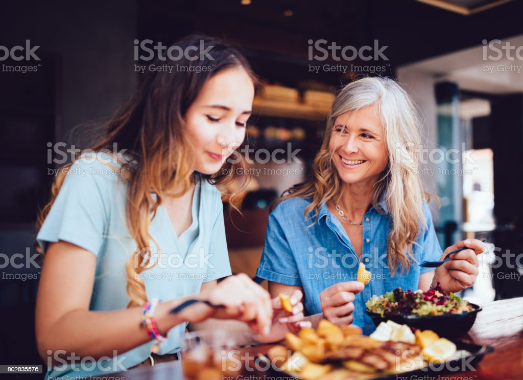 Beautiful senior mother and daughter eating lunch together at restaurant stock photo