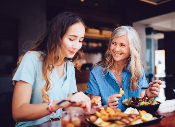 beautiful senior mother and daughter eating lunch together at restaurant - family dinner stock photos and pictures