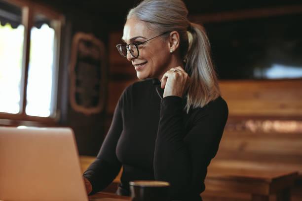 dizüstü bilgisayar kullanan cafe'de güzel kadın kıdemli - kır saç stok fotoğraflar ve resimler