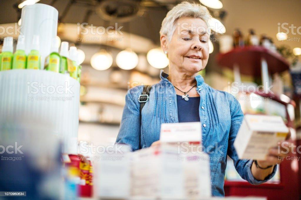 Schöne ältere Frau Medizin in Apotheke kaufen – Foto