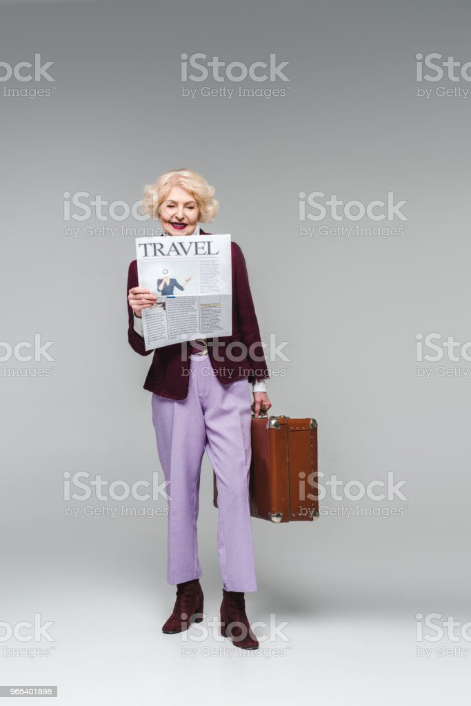beautiful senior woman holding suitcase and reading travel newspaper on grey zbiór zdjęć royalty-free