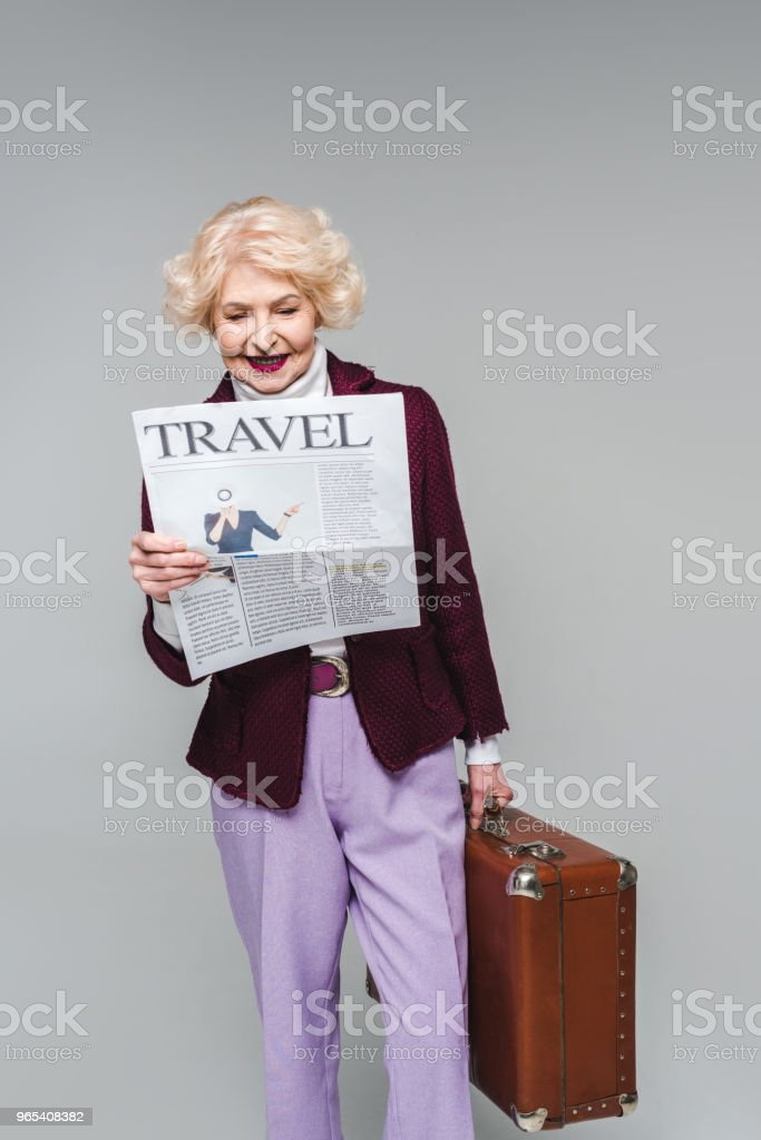 beautiful senior woman holding suitcase and reading travel newspaper isolated on grey royalty-free stock photo