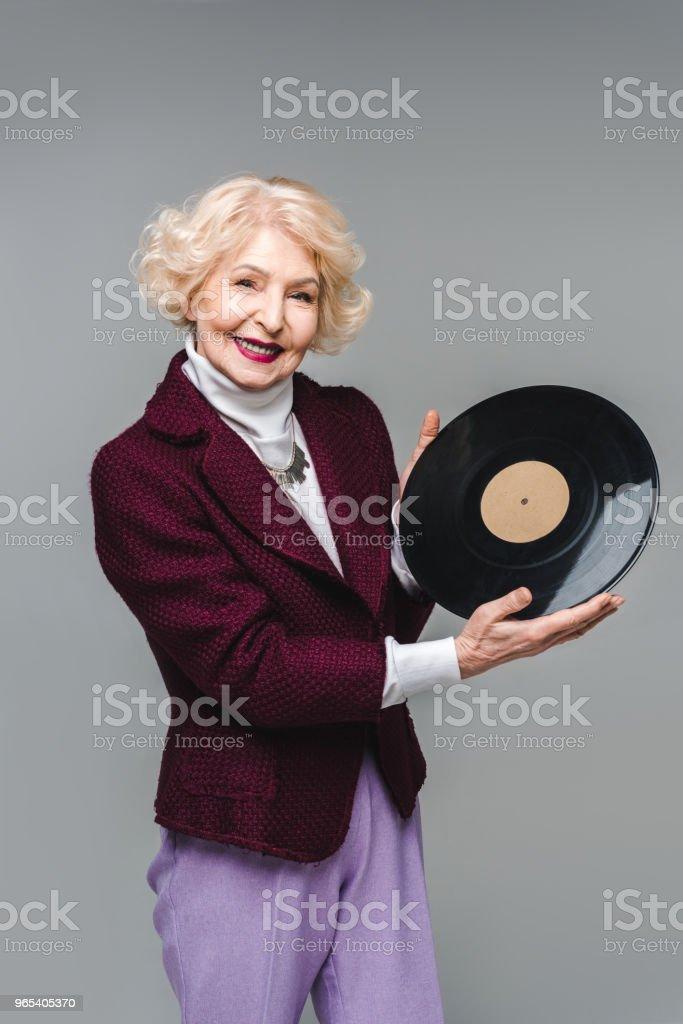 美麗的資深婦女持有乙烯基光碟孤立的灰色 - 免版稅一個人圖庫照片