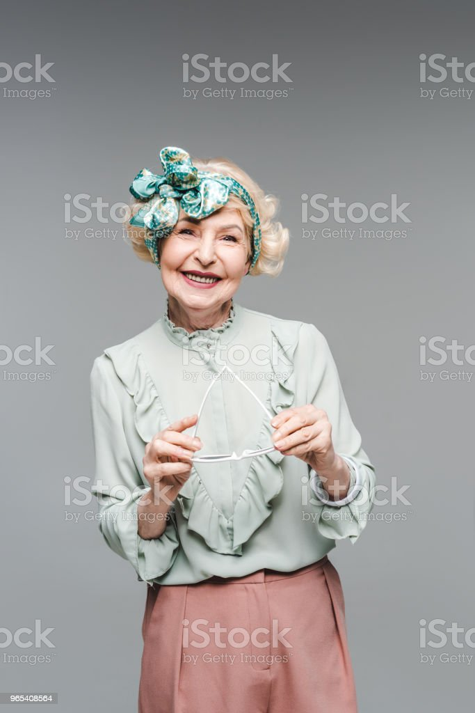 beautiful senior woman in stylish clothes holding sunglasses isolated on grey royalty-free stock photo