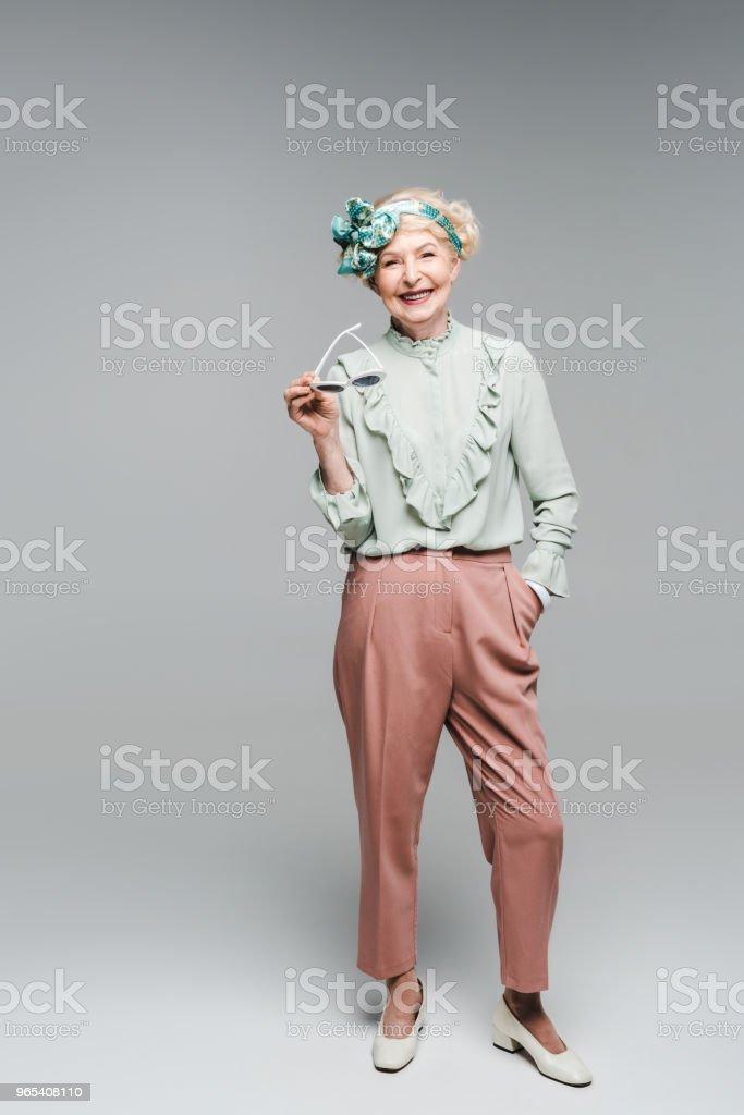 beautiful senior woman in stylish clothes holding sunglasses on grey zbiór zdjęć royalty-free