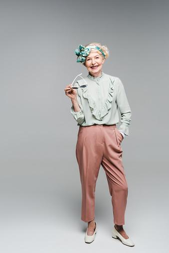 회색에 선글라스를 들고 세련 된 옷을 입고 아름 다운 수석 여자 노인에 대한 스톡 사진 및 기타 이미지