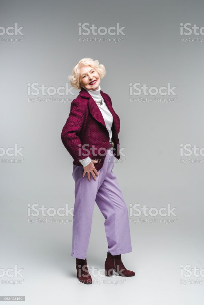 beautiful senior woman in stylish clothes looking at camera on grey zbiór zdjęć royalty-free