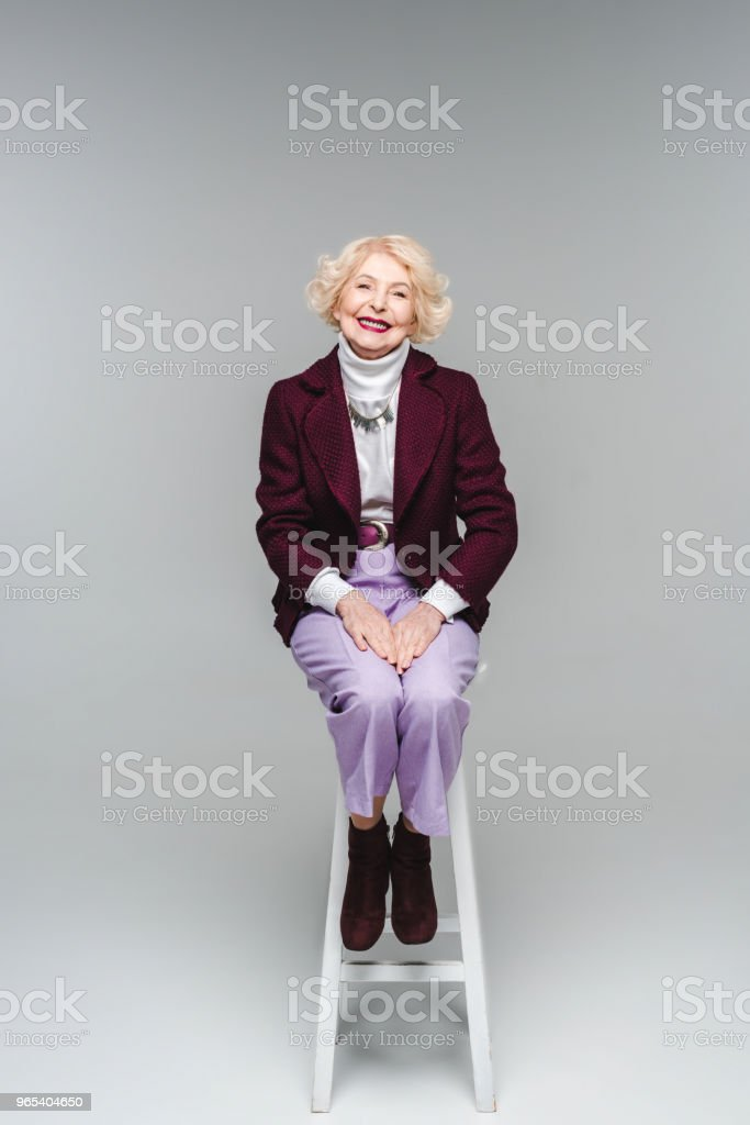 beautiful senior woman in stylish clothes sitting on chair on grey royalty-free stock photo