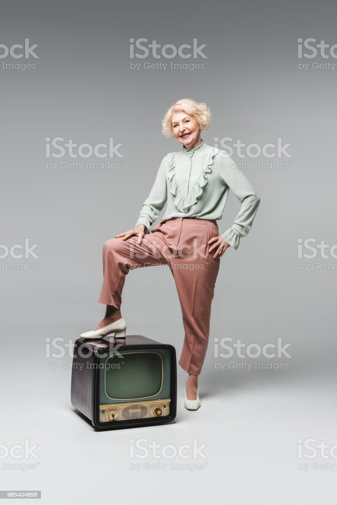 beautiful senior woman in stylish clothes with feet on vintage tv on grey zbiór zdjęć royalty-free
