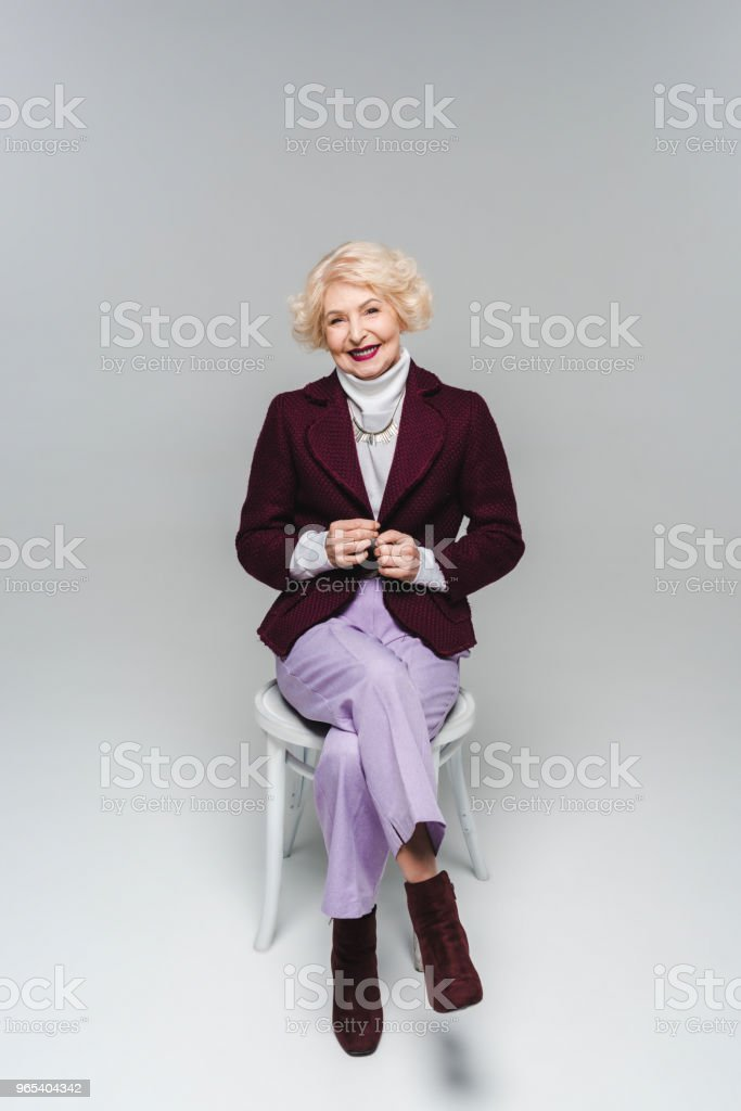 beautiful senior woman in stylish jacket sitting on chair and looking at camera on grey royalty-free stock photo