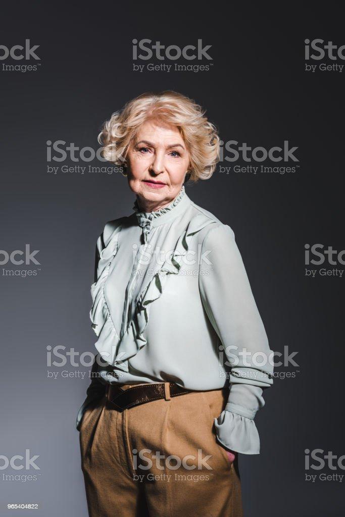 beautiful senior woman in stylish shirt looking at camera on dark grey zbiór zdjęć royalty-free