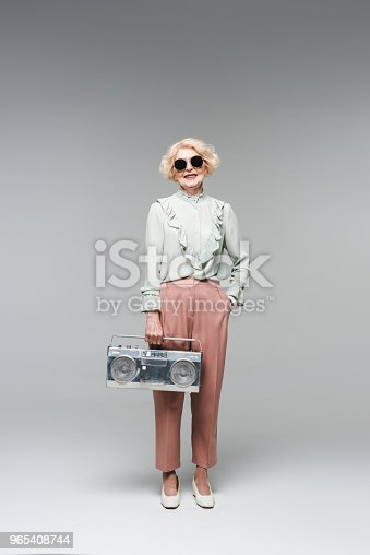 Beautiful Senior Woman In Stylish Sunglasses With Vintage Boombox On Grey Stock Photo & More Pictures of Adults Only