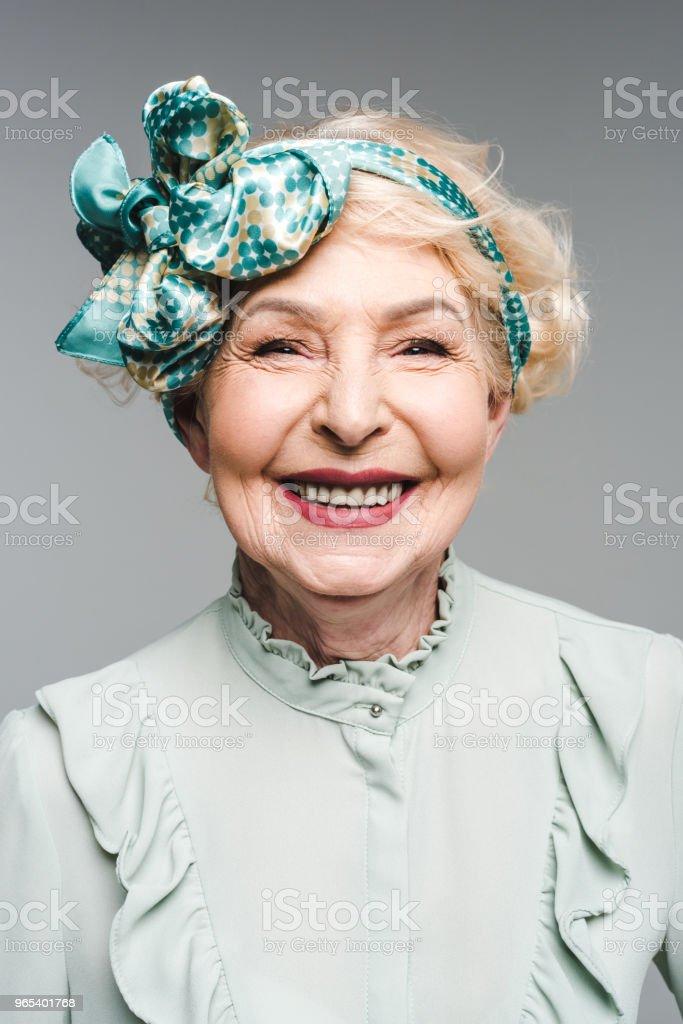 beautiful senior woman in stylish vintage shirt and headband isolated on grey zbiór zdjęć royalty-free