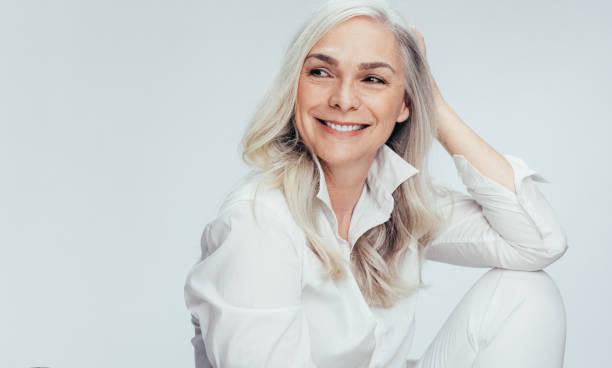 vacker senior kvinna tittar på kopierings utrymme - mature women studio grey hair bildbanksfoton och bilder